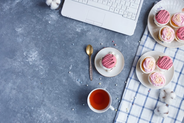 On the gray table is a laptop, a plate of cream cakes, a cup of tea