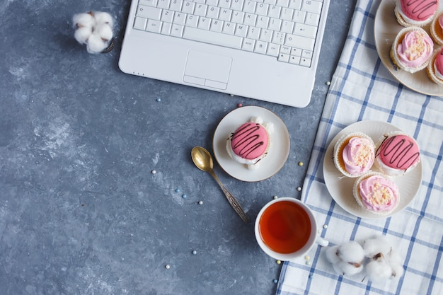 On the gray table is a laptop, plate of cream cakes, cup of tea