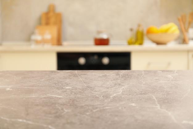 Серый стол на размытом фоне интерьера кухни