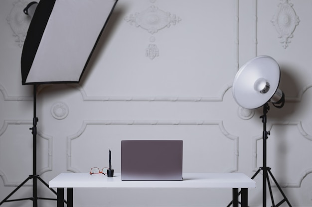 A gray table stands at a photo studio surrounded by professional lighting a laptop glasses are on the table