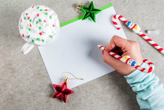 A gray table with a greeting sheet, christmas decorations, a cup of hot chocolate and pen in form of candy cane. girl writing, female hand in picture,  top view