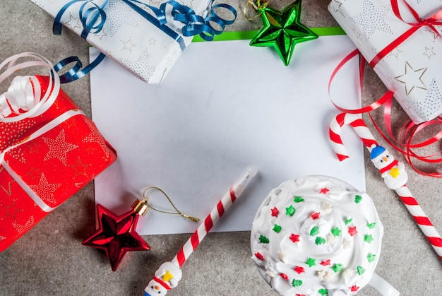 A gray table with a greeting sheet, christmas decorations, a cup of hot chocolate and pen in form of candy cane