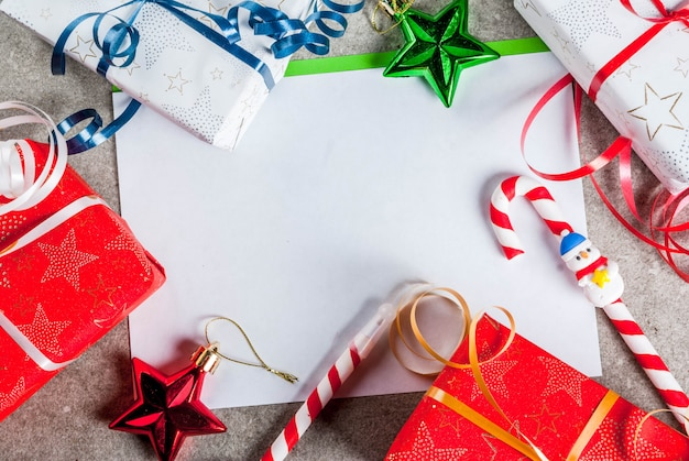 A gray table with a greeting sheet, christmas decorations and gift boxes, a cup of hot chocolate and pen in form of candy cane.  top view