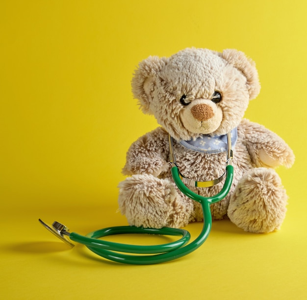 Gray teddy bear and green medical stethoscope on a yellow