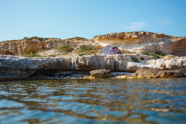 Gray tent on a rocky seashore. view from the water