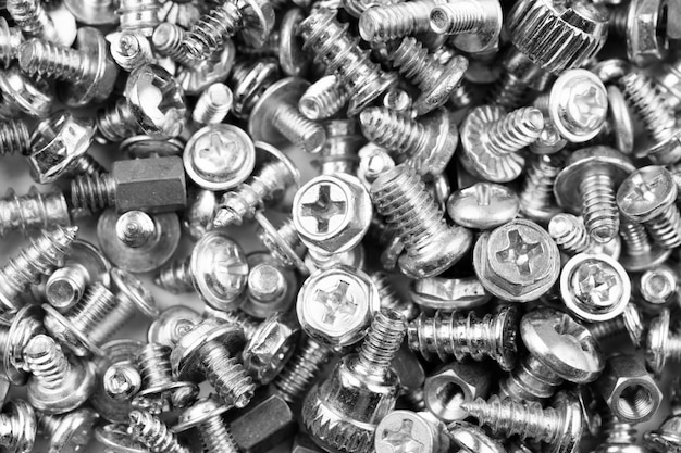 Gray texture background of many randomly scattered computer screws
