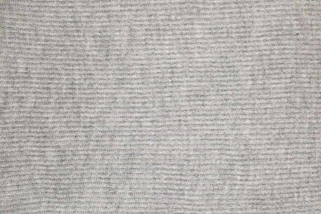 グレーの風合いのニットウールの表面。背景、繊維からの壁紙。暖かい生地。高品質の写真