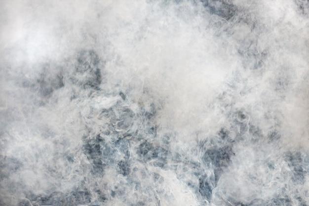 灰色の濃い煙。暗闇の中で朝の霧