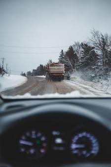 Серый грузовик убирает снег на дороге в дневное время