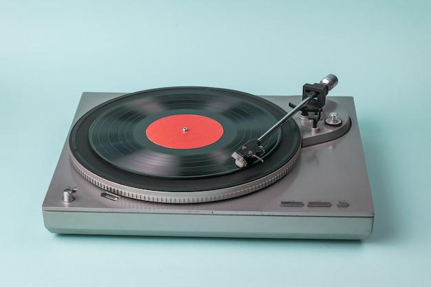 파란색 배경에 회색 턴테이블입니다. 음악 재생을위한 복고풍 장비.