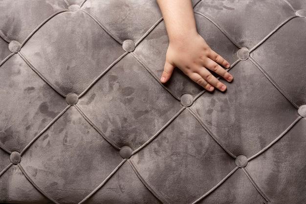 子供の手と灰色のビロードのソファのテクスチャ背景