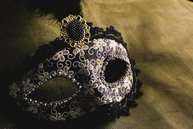 Gray venetian mask on a yellow fabric