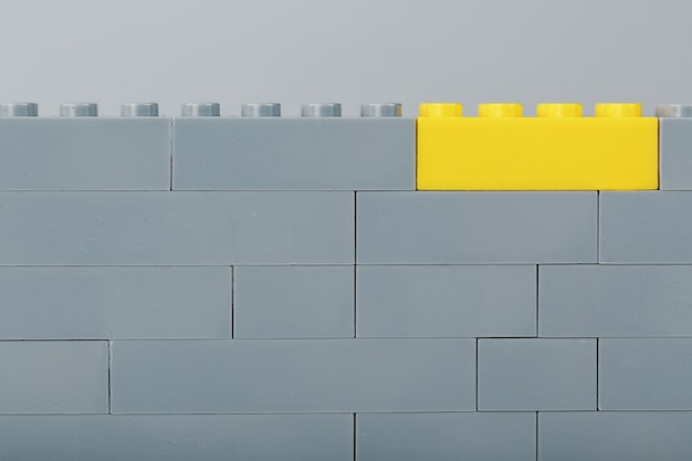 A gray wall made of a toy construction set with the last yellow brick