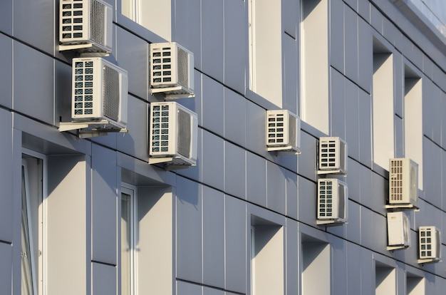Gray wall of office building made of metal plates with windows and air conditioners