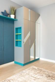 美しい装飾が施された部屋の中に青い棚と鏡が付いた灰色のワードローブ
