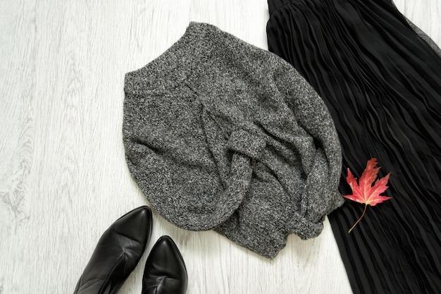 グレーの暖かいセーター、黒いスカートとブーツ。ファッショナブルなコンセプト
