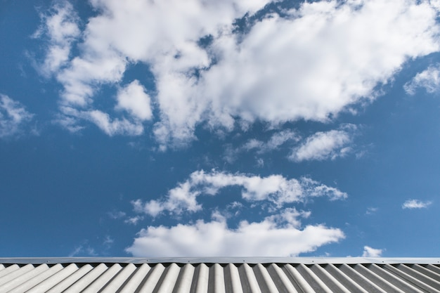 Gray wavy slate roof and blue sky with white clouds. beautiful cloudscape