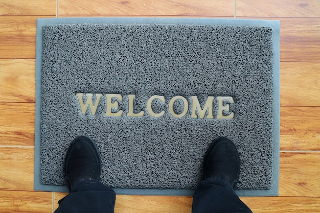 A gray welcome doormat with feet wearing black shoes