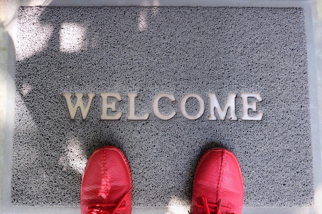 A gray welcome doormat with feet wearing red shoes