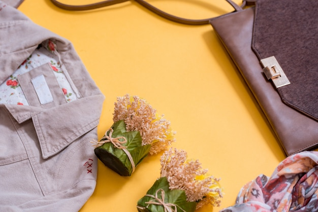 Gray with silvery female sneakers, scarf and bag on a bright yellow background. autumn fashion concept. top view, flat lay