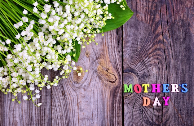 Gray wooden background with the inscription mother's day