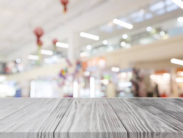 Gray wooden desk in front of illuminated shopping center