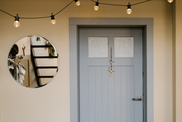 Серая деревянная входная дверь в дом и зеркало рядом с ней