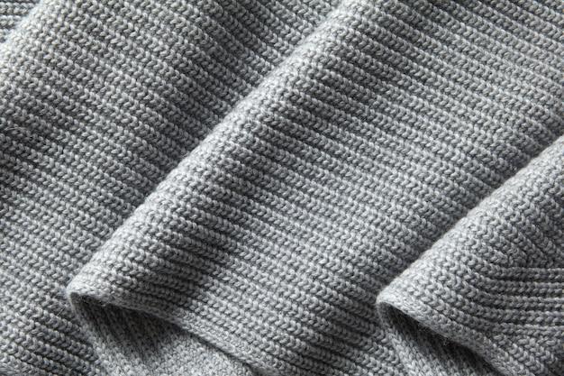 회색 모직 니트 직물 접기. 자연스러운 드레이프 니트 질감