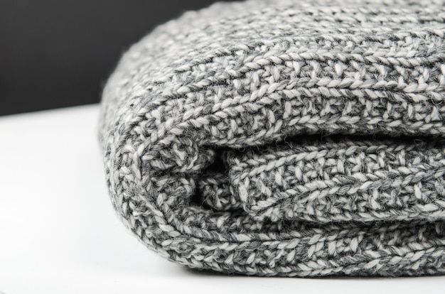 Gray wool knitted plaid, lies rolled up on white table. close up.