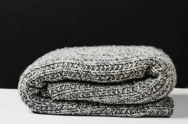 Gray wool knitted plaid, lies rolled up on white table.