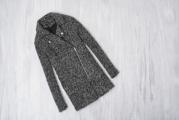 Gray woolen coat on wooden background. fashionable concept