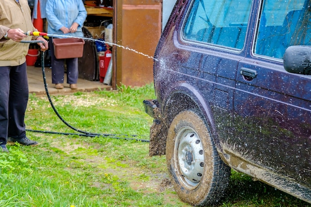 A grayhaired elderly man washes a car outdoors with a garden hose