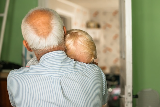 Grayhaired grandfather with a blondhaired girl in arms grandfathers and granddaughters head is close
