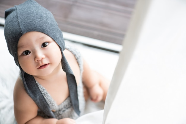 A grayhatted baby sitting on the floor is looking up with his face sticking out between the curtain