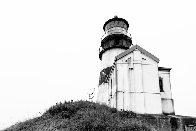 Grayscale low angle shot of a lighthouse near a small cabin on a cliff