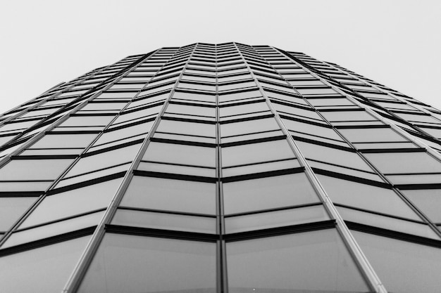 Grayscale low angle shot of modern glass building