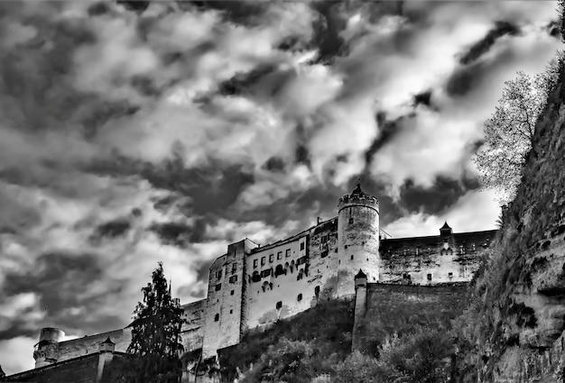 잘츠부르크, 오스트리아에서 흐린 하늘을 배경으로 호엔 잘츠부르크 성의 그레이 스케일 낮은 각도 샷