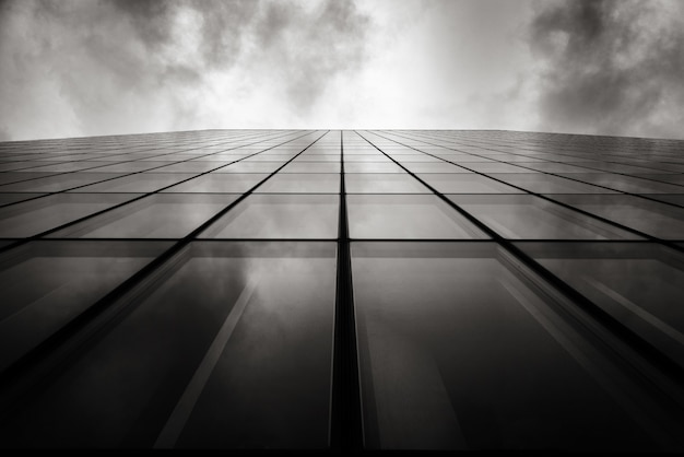 Grayscale low angle shot of a skyscraper a wall with glass windows under the cloudy sky