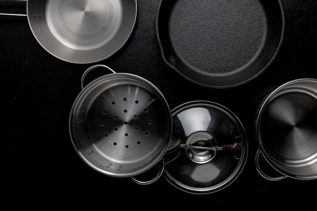 Grayscale overhead shot of metal pot frying pan a lid