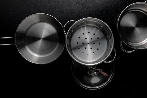 Снимок металлической сковороды с крышкой в оттенках серого