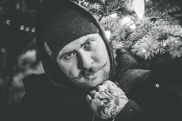 Foto in scala di grigi dell'uomo in berretto e felpa con cappuccio