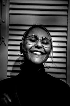 タートルネックのトップを着て笑顔の女性のグレースケール写真