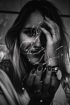 Фотография женщины, держащей гирлянды в оттенках серого