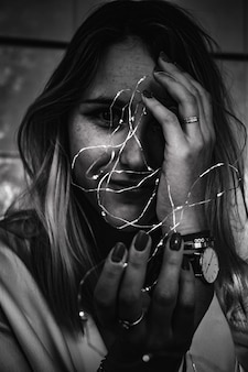 Grayscale photo of woman holding string lights