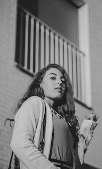 Foto in scala di grigi della donna accanto a casa