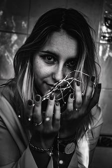 Fotografia in scala di grigi della donna che tiene le luci della stringa