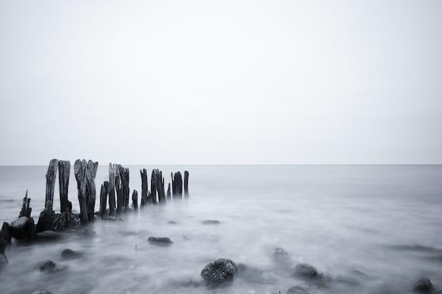 Scatto in scala di grigi di una bellissima vista sul mare sotto un cielo nuvoloso a ostsee, germania