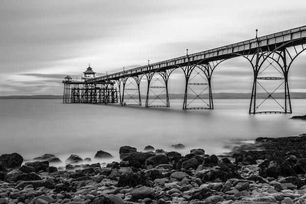 Scatto in scala di grigi di un ponte su un lago e pietre sulla baia in una giornata nuvolosa