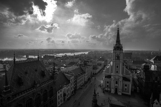 Grayscale shot of buildings in torun city in poland with a cloudy sky in the background