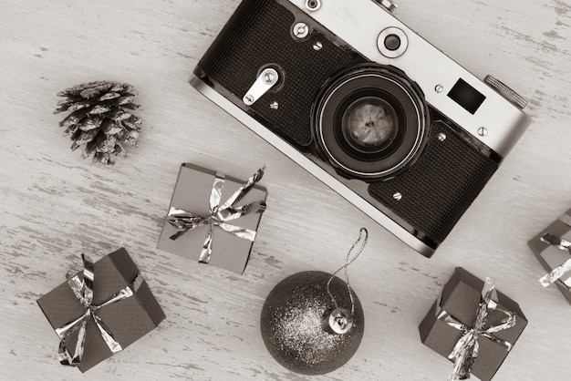 Grayscale shot of christmas gift boxes and camera